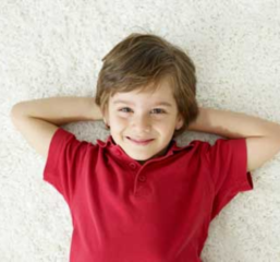 boy lying down on a carpet that was just steam carpet cleaned
